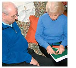 A carer reading a book to a man